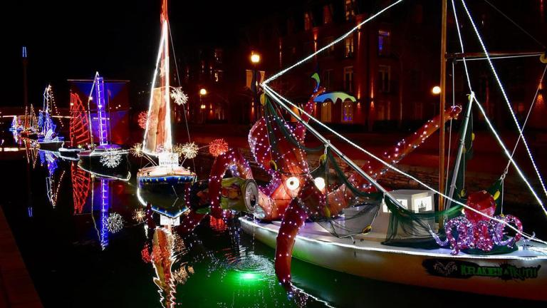 Boats decorated with holiday lights in creek