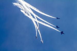 Blue Angels dive leaving dramatic white trails of smoke in the sky
