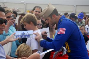 A Blue Angels pilot signs the tee shirt of a young air show fan