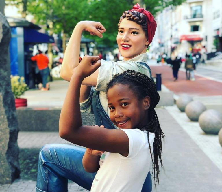 girl posing with Rosie the Riveter statue