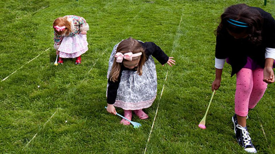 Three young ladies participating in an Easter Egg Roll race.