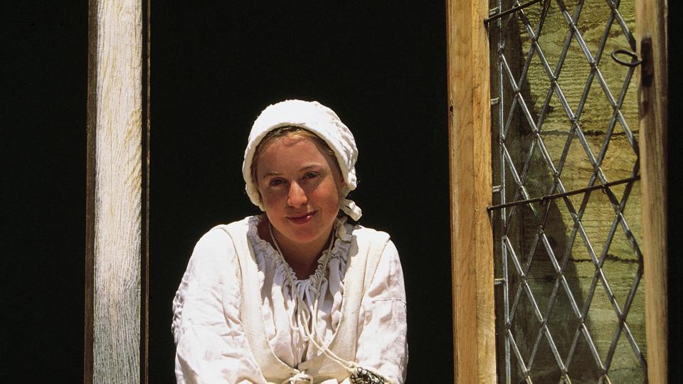 Women in a window dressed in colonial attire
