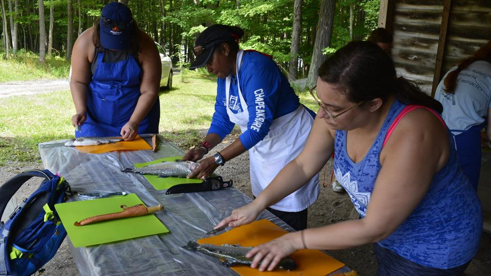 Participants from Becoming an Outdoors-Woman Prepare Fish They Caught