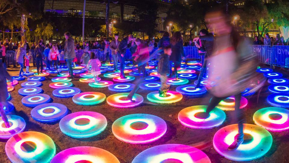 People dancing on lighted pads
