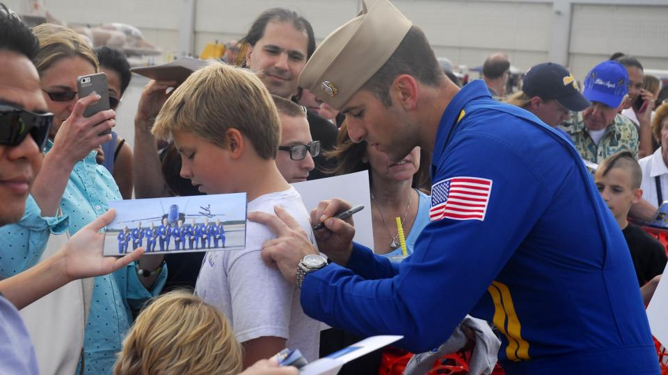 A Blue Angels pilot signs a young fan's tee shirt at Martin State Airport after the air show
