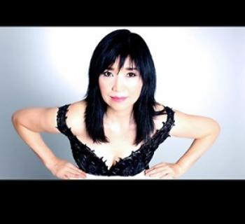 Keiko Matsui wearing a black dress and looking at the camera directly Photo