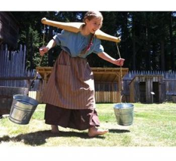 Girl in pioneer clothing carries two water pails Photo