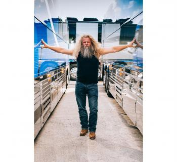 Jamey Johnson poses with two tour busses Photo