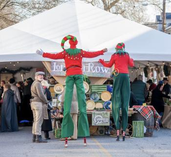 Stiltwalkers visit the vendor tent during Dickens of a Christmas.  Photo