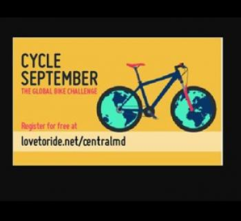 Cycle September poster with yellow background and bike outline with world map on front and rear whee Photo
