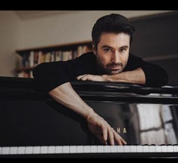 Dan Tepfer with a piano Photo