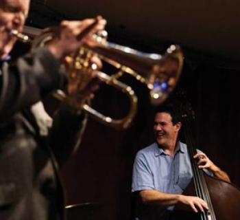 A man plays trumpet while a man playing bass smiles Photo