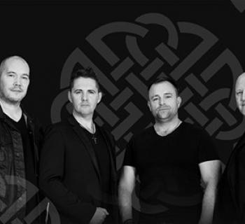 The High Kings against a dark background with a Celtic Symbol on the wall Photo