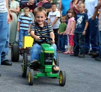 boy on toy tractor Photo