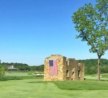Picture of a fairway that has a stone wall with an American flag hanging along the side. Photo