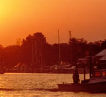 Photo of boats on the water at sunset Photo