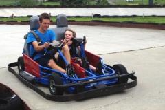 Man and child riding in a go kart