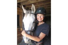 A smiling rider with a horse at New World Stables