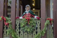 Lady on wreath wrapped balcony