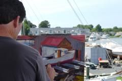 Man works on a painting of a boat on the Eastern Shore