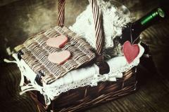 Picture os a basket with a bottle of wine and some pink heart shaped chocolates on top