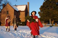 woman walking through snow in red cape