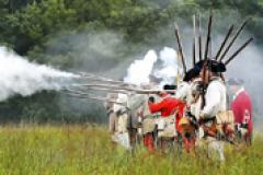 18th Century French, Indian and British reenactors lined up firing their rifles