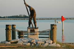 A statue of a waterman hand tonging for oysters
