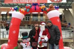 Young man and woman standing with santa claus