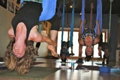 Small group practicing aerial yoga