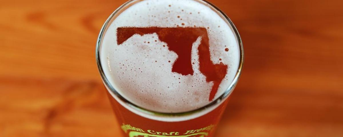 Glass of Evolution Craft Beer with foam that forms Maryland map