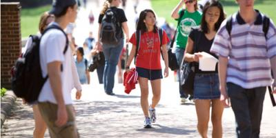 Female students wearing a red 'Fear the Turtle' t-shirt walking in a crowd of people on the sidewalk near the Mall.
